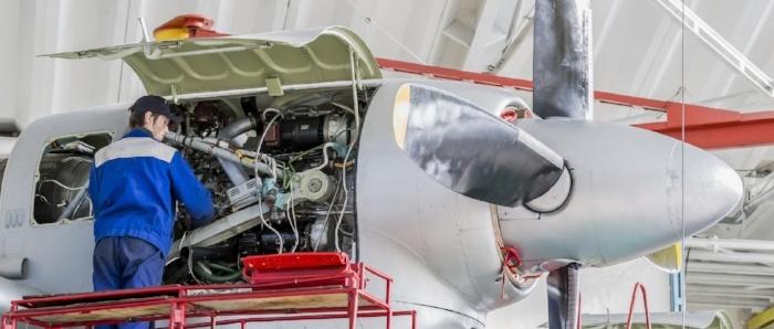 Aviation Engineer Repairing Jet Engines in Aircraft Hangar