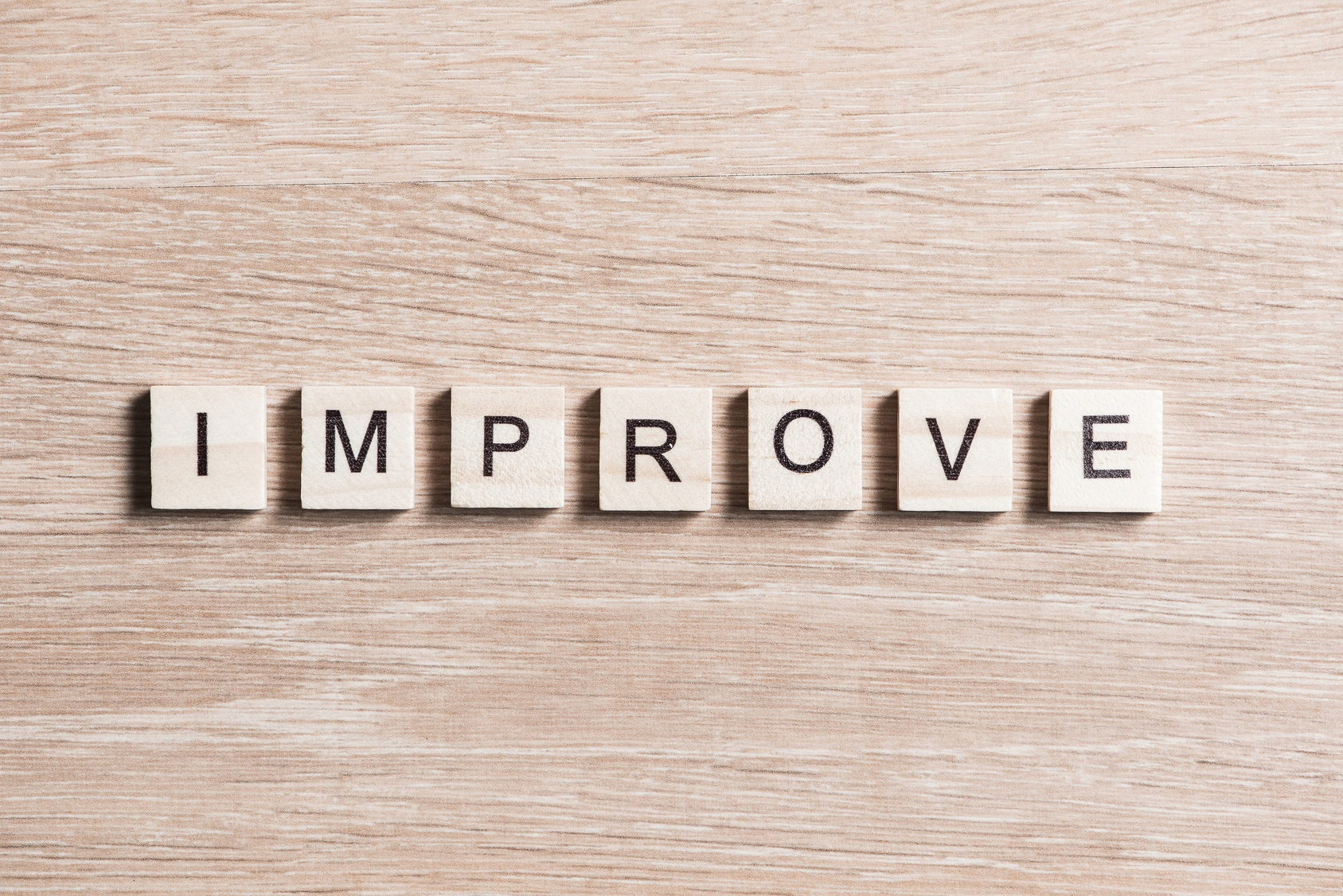 Seven Wood Tabs Spelling Out the Word Improve