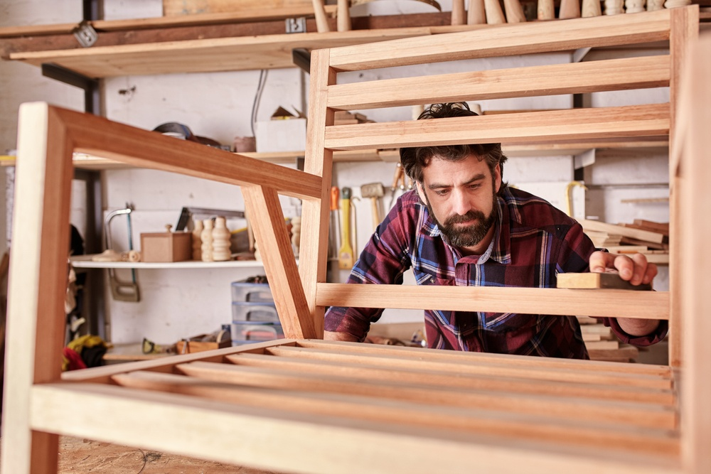 American Furniture Craftsman Touches Up the Finish on Wood Chair