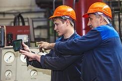 senior_factory_worker_teaching_younger_employee